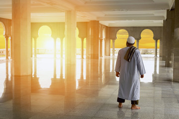Muslim people praying with harsh sunset in mosque interior background