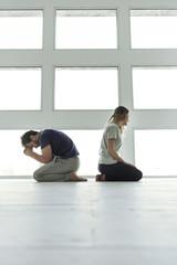 Pensive married couple sitting on floor
