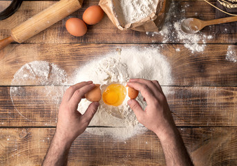 Wall Mural - Male hands beat the egg yolk into the flour