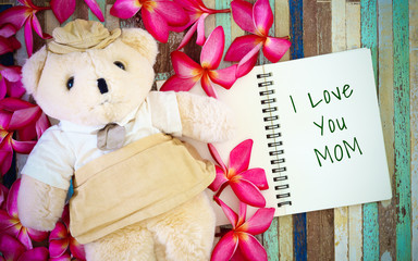 Mothers day greeting card concepts with I love you Mom text and cute Teddy bear doll. Top view on wooden background.