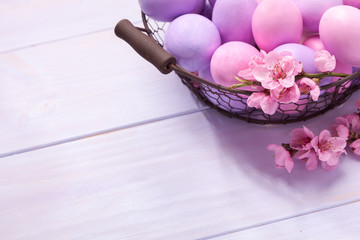 Easter eggs and   blooming peach branch on   wooden table.