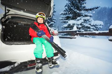 Boy skier sitting in the car trunk during snowfall
