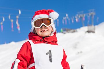 Portrait of cute boy in Santa's hat at snowy hill