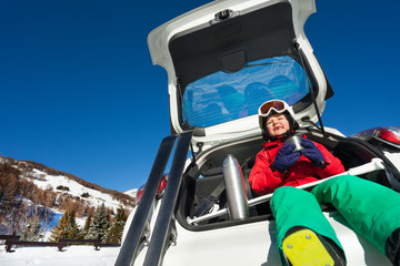 Skier sitting in car boot and drinking warm tea