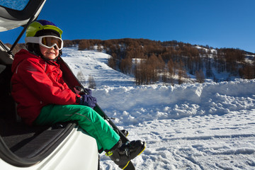 Smiling boy, little skier sitting in the car boot
