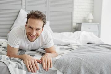 Carefree guy resting in bedroom