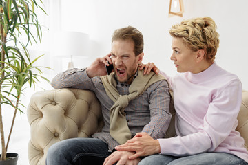 Irritated guy speaking on smartphone near his wife