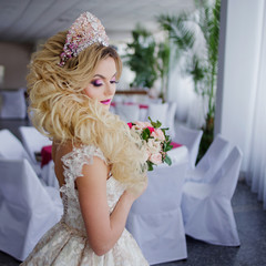 Young fashion bride with perfect skin and make up, curly hair, flowers and tiara on the head, indoors