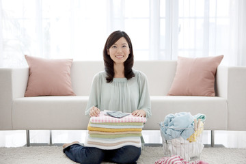 Young woman folding laundry
