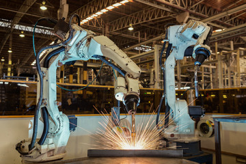 Team robots are welding assembly part  in car factory
