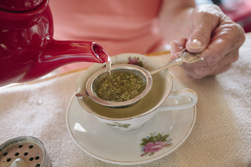 Close up of woman's hand straining cannabis tea in cup