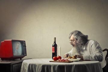 Elderly man watching tv at lunch