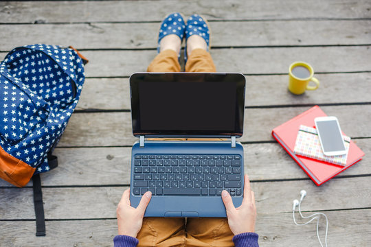 Top view of young hipster girl using laptop outdoor