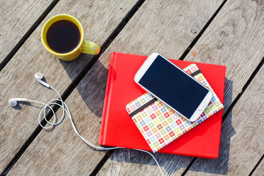 Working place with coffee cup, smartphone, headphones, stacked books on wooden background