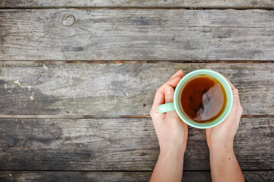 woman holding hot cup of tea on wooden background
