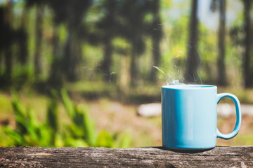 Cup of coffee or tea on plank wood with green nature background