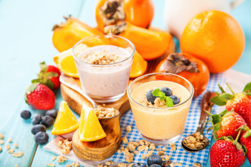 Orange persimmon blueberry smoothie with granola  and fruits. Selective focus. Copy space