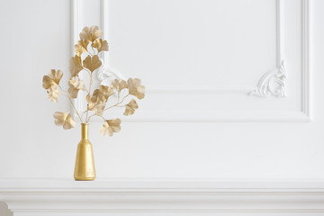 white interior. A white fireplace in a light interior and a gold vase. Classical interior