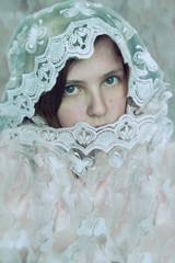 Retrato artístico de una chica joven cubierta con un velo de encaje