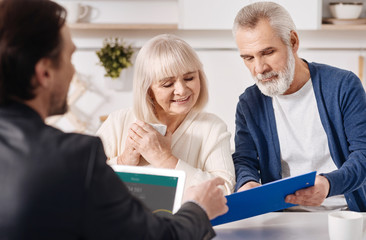 Real estate advisor working with aged couple in the house