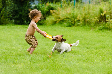 Happy boy playing with dog active game on lawn