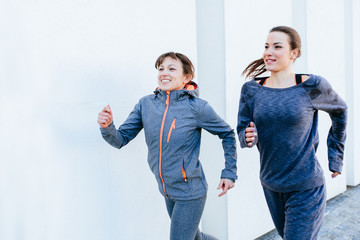 Two sporty women jogging outside over white background. Healthy lifestyle and sport concepts