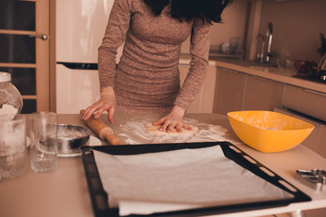 Woman rolling dough with pin on table. Making cookies in kitchen.