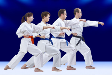 On a dark blue background four adult athletes are beating punch arm