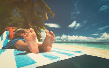 little boy relax at summer beach, focus on feet