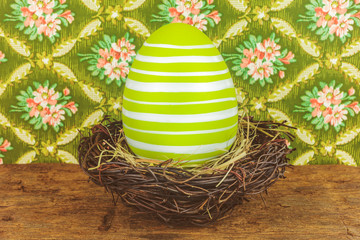 Green dyed big easter egg in a bird nest on a wooden table