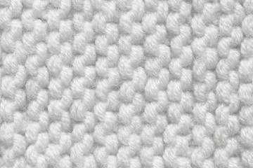 Knitted texture of white color. Hand-made knitting needles for postcard background. Winter cozy thing.
