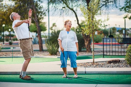 retired couple having fun playing mini golf