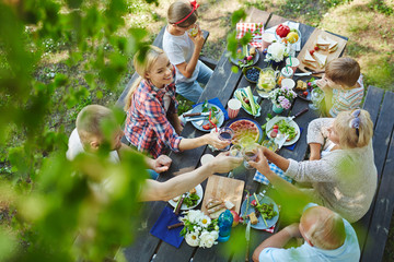 Adults toasting with wineglasses by served table during family dinner Wall mural