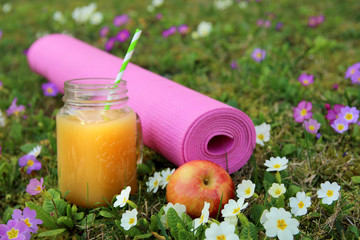 Yoga mat on green grass with flowers. Jar with juice. Spring. Apple. Concept of sports. selective focus.