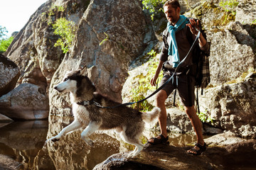 Young handsome man walking with huskies dog in canyon near water.