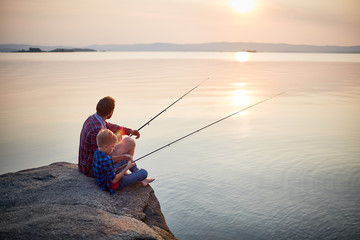 Ingelijste posters Vissen Back view portrait of father and son sitting together on rocks fishing with rods in calm lake waters with landscape of setting sun, both wearing checkered shirts