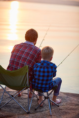 Back view portrait of father and son sitting together on rocks fishing with rods in calm lake waters in sunset light, both wearing checkered shirts