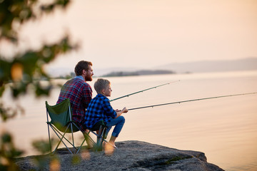 Side view portrait of father and son sitting together on rocks fishing with rods in calm lake waters with landscape of setting sun, both wearing checkered shirts, shot from behind tree Wall mural