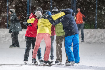 Group of young people embrace on a skating rink