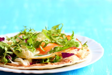 Homemade tortilla with fried egg, salad mix, hummus and parsley on a plate. Blue wooden background. Healthy and quick tortilla with filling. Closeup