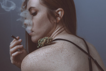 Young woman smoking joint with cannabis bud on her shoulder