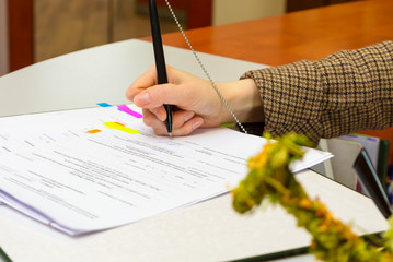 A woman at the office signing a contract with a shallow focus on the signature.