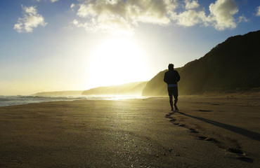 Young man walking down Johanna beach alone on sunset