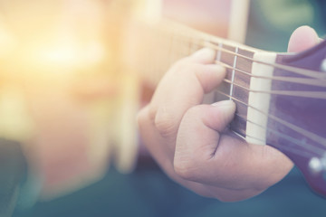 Relaxing Musical concept,Practicing in playing guitar. Handsome young men playing guitar,man's hands playing acoustic guitar, close up,selective focus,vintage color