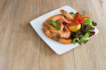 Shrimp boiled with honey and salt in white dish on dark table thai food