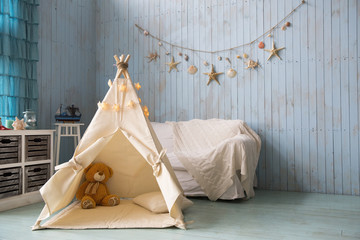 Teddy bear sits in a children's house wigwam. on the background of an old wooden blue wall