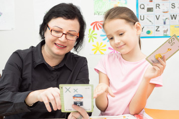 Woman teacher and school girl study with flash cards