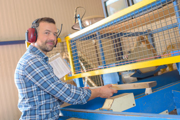 Man working with wood behind screen