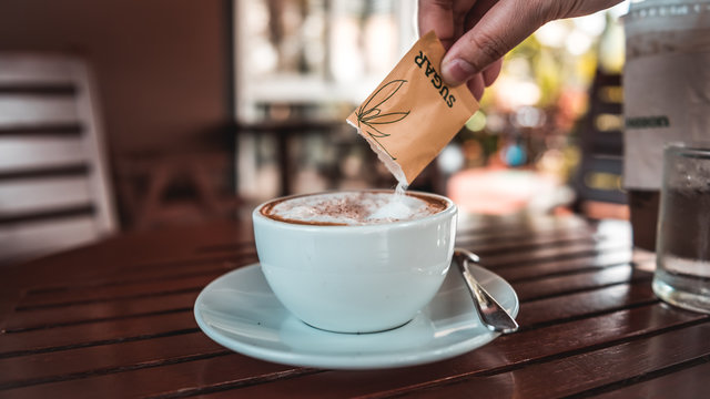 Hand pouring a sugar packet into a cup of coffee.