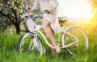 Beautiful female cyclist with retro bicycle in the spring garden